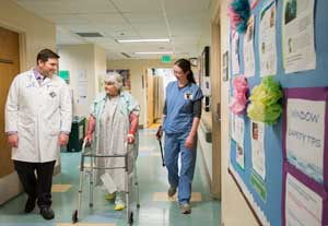 Two clinicians walking a patient down the hallway